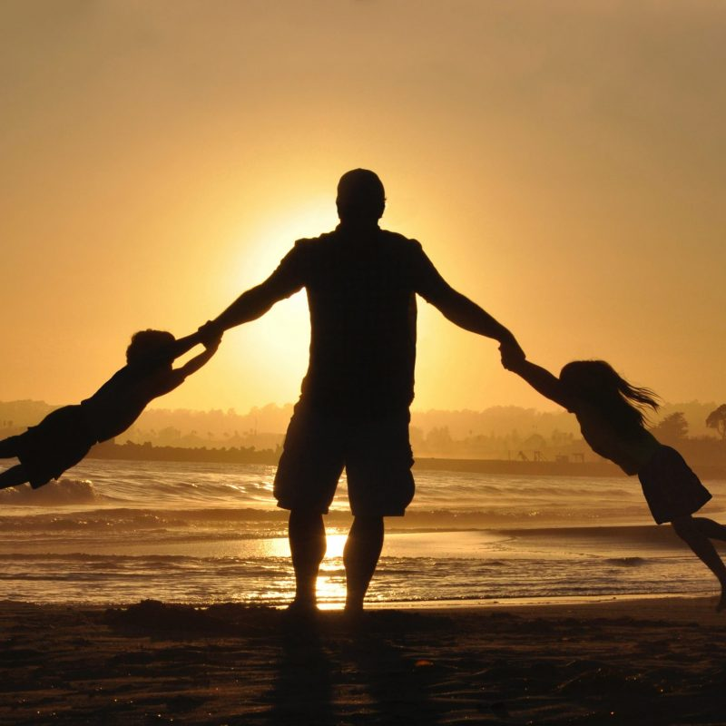Father plays with children at a family gathering on a beach in Sicily